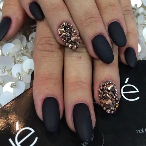 Фото красивого матового покрытия ногтей овальной формы с крупными стразами золотого и черного цвета